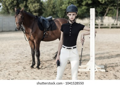 Jumping over obstacles. Horserace concept. Beautiful woman near hourse. Outdoor shot, sport and fashion concept.