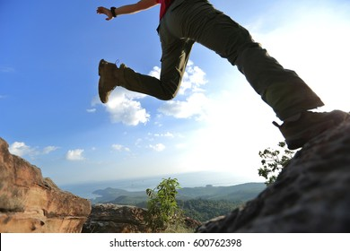 jumping over precipice between two rocky mountains. freedom, risk, challenge, success concept