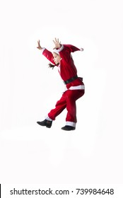Jumping Santa. Little caucasian girl dressed as Santa Claus getting down after jump on white background. Copy space.