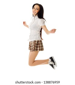 Jumping school girl in plaid skirt and sneakers isolated
