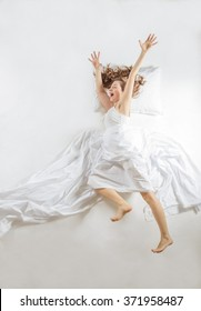 Jumping sleeper dressed in white with white sheets, shot from top, studio shot against light background. Expressive woman in action, dreaming concept.