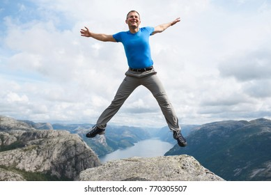 jumping smiling man at lysefjord in norway