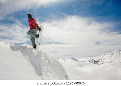 Jumping snowboarder keeping his one hand on the snowboard on the amazing blue sky background