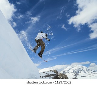 Jumping snowboarder in mountains on the snowboard on blue sky background