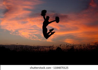 Jumping Teenage Girl Cheerleader Joyful Silhouette at Sunset
