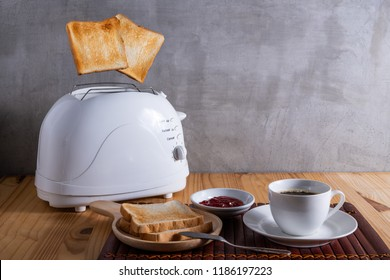Jumping toasted breads from the toaster  being served with jam and a cup of coffee on the wooden table for breakfast