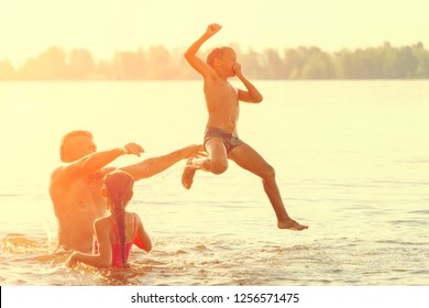Jumping in the water. Man with children are having fun and splashing in the water. Summer holiday concept