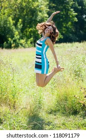 Jumping    woman  against summer meadow