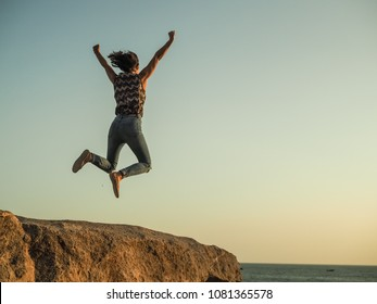 jumping WOMAN celebrates her triumph WITH arms up on top of a rock at the beach