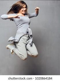 Jumping woman wearing sports wear. Gray wall back.