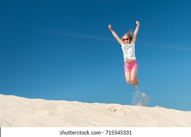 Jumping young girl in front of blue sky