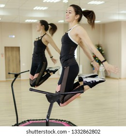 Jumping young woman in trampoline sport center indoors.Mini Trampoline Workout: Girl doing Fitness Exercise in Class at Gym