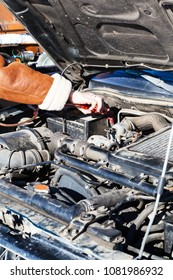 Jumpstart a dead car battery with another vehicle and jumper leads in cold winter day