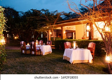 JUN 20, 2011 Serengeti, Tanzania - Luxury African Safari lodge outdoor dining on grass lawn with leather chairs white tables fine dining setting and warm light from lamps at twilight time
