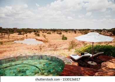 JUN 20, 2011 Tanzania - Swimming pool African Luxury Safari lodge terrace with white umbrella and pool bed in Savanna forest of Serengeti Grumeti wildlife Reserve.