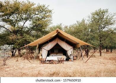 JUN 22, 2011 Serengeti, Tanzania - Luxury Safari tent camp in Serengeti Savanna forest Grumeti reserve game drive area  - Glamping travel in Africa wild forest