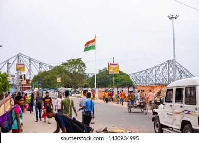 Juna 20,2019.Kolkata, India. A view from Howrah Railway station of The Heritage Howrah bridge or Rabindra Setu with indian flag flying in the clear blue sky.