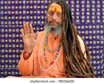 JUNAGADH, GUJARAT / INDIA - FEB 22, 2017: Middle-aged Indian sadhu with very long dreadlocks raises his right hand with the palm forward to give a blessing during Bhavnath Fair, on Feb 22, 2017.