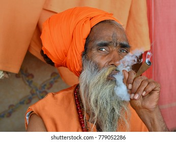 JUNAGADH, GUJARAT/INDIA - FEB 21, 2017: Old Indian Hindu holy man (sadhu) with orange turban smokes hashish (marijuana) in a chillum pipe during Shivratri Mela, on Feb 21, 2017.