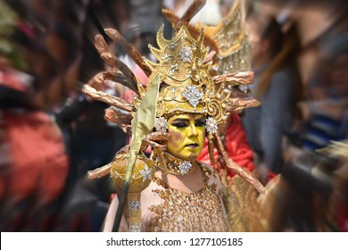 June 1, 2018. Beautiful young girl is wearing a Lernaean Hydra golden costume and is participating in the parade Fiesta de los Locos in San Miguel de Allende, Guanajuato Mexico.