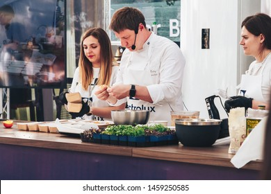 June 1, 2019 Minsk Belarus Public demonstration of cooking on the street The chef of the Swedish company prepares food Two Two beautiful assistant girls help the cook