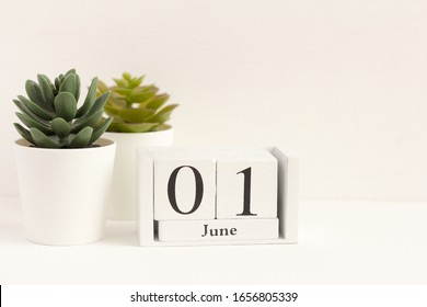 June 1 on a wooden calendar on a light background with flowers. First day of summer. Empty space for text. June 1 is children's day.Hello summer.