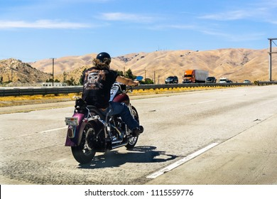 June 10, 2018 Los Angeles / CA / USA - Biker riding a Harley Davidson motorcycle on the interstate; golden hills and blue sky in the background