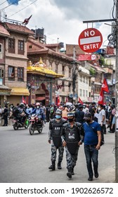 """June 14, 2020, Kathmandu, Nepal. AFP Special Forces police walking under sign """"No entry"""", along a street full of demonstrators protesting corruption and ineffective fight against coronavirus in Nepal."""