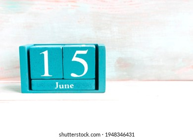 June 15. Blue cube calendar with month date isolated on wooden background.
