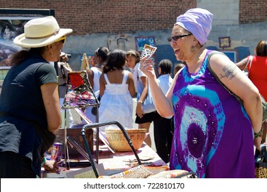 June 16, 2012 - Philadelphia, PA, USA:  African-American women haggle over the price of handcrafted goods at an outdoor African-American Art Expo in Philadelphia, Pennsylvania.