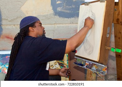 June 16, 2012 - Philadelphia, PA, USA:  An African-American artist draws a new art work  to sell at an outdoor African-American Art Expo in Philadelphia, Pennsylvania.