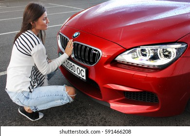 June 16, 2015; Kiev, Ukraine; Beautiful girl sitting near the BMW car.  It's raining. The girl and the car wet. Editorial photo.