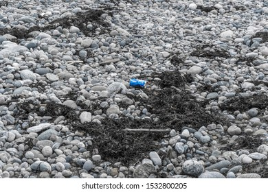 June 16, 2019 - Cow Head, Newfoundland, Canada: A blue Pepsi pop can lays discarded as litter on a stony beach - a problem for the ocean and surrounding natural environment. Illustrative editorial.
