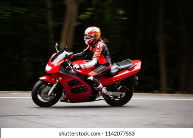 June 19, 2016; Moscow district, Russian Federation: Biker girl on a sportbike in a turn on a country road