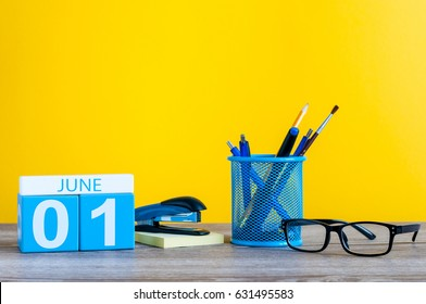 June 1st. Day 1 of month, calendar on business office table, workplace at yellow background. Summer time