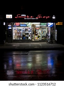 June 2, 2018 - New York, NY, USA - Smoke Shop neon lights reflect in wet streets of New York