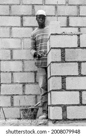 June 2, 2021 Naranjal, Dominican Republic. Dramatic black and white image of a Haitian construction worker installing cement blocks on a job site in Caribbean mountains.