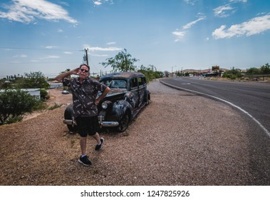 June 20, 2017 - Tombstone, Arizona, USA. Man goofing around in front of the famous hearse of Boothill Graveyard.