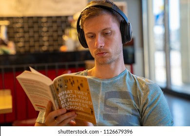 June 20, 2018. Valletta, Malta. Young man sitting in the cafe with earphones reading a book about Harvard.
