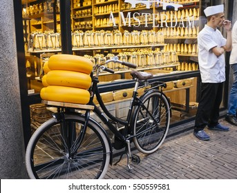 June 2016 Amsterdam, Netherlands: Amsterdam. shop of Dutch cheeses with bike stacks of cheese on display outside the shop and the shopkeeper smokes a cigarette during a break