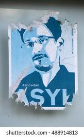 JUNE 2016 - BERLIN: an image of Edward Snowden on an already faded sticker demanding granting him asylum in Germany, Berlin.