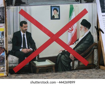 JUNE 2016 - BERLIN: a protest poster with a photo of a meeting of Iranian President Hassan Rohani (Rouhani) and Syrian dictator Baschar Hafiz al Assad at a demonstration in Berlin.