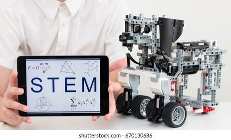 June, 2017. Belarus, Minsk. Cyber Lego dog. Robot. Robotics. Symbol of New year 2018. Teenager boy holds Ipad Apple. STEM education.