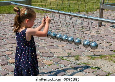 June, 2017. Krakow. Poland. Museum of Science in the open air. Park. A little sweet girl looks at the pendulum of metal balls. STEM education. Back to school.