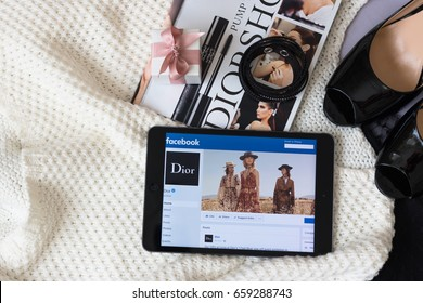 June, 2017. Minsk, Belarus. Pandora jewelry box. Black shoes in lacquered leather. Magazine opens on page with Dior advertising. On Apple Ipad, the page of the famous Dior brand in Facebook.