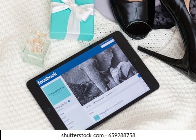 June, 2017. Minsk, Belarus. Tiffany jewelry box. Perfume. Fashionable black shoes in lacquered leather. Knitted sweater. On Apple Ipad, the page of the famous Tiffany brand in Facebook.