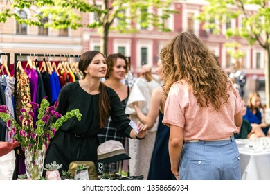 June 2018, Creative Space New Holland, Saint-Petersburg, Russia. People on the summer outdoor vintage fashion designer market. Garage sale, reuse the clothes, second hand and eco consumer