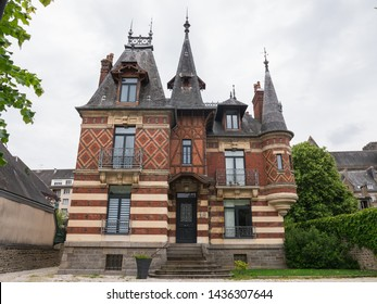 June 2019. Beautiful french mansion made of stone & bricks in a town named Flers (Normandy, France). Rue Richard Lenoir. Magnificent piece of architecture. Cloudy day. Low-angle. Potter style manor