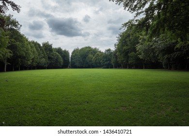 June 2019. Beautiful landscape shot in the park of Flers's castle (Orne, Normandy, France). Lawn surrounded by forest on a cloudy day. Very scenic photography. Dreamy shot. Wide-angle & sharp.