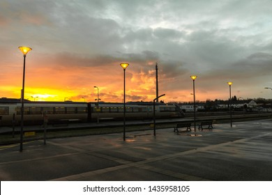 June 2019. Beautiful sunset at the Flers's train station (Normandy, France). Magnificent sunlight with clouds. Street lights are on. Wide-angle shot. Train in front of the platform.
